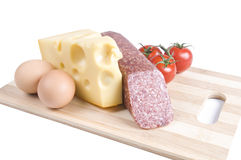 Eggs, cheese, sausage and tomatoes on a board Royalty Free Stock Images