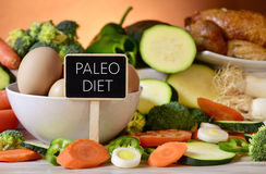 Eggs, chicken, vegetables and text paleo diet. Closeup of a signboard with the text paleo diet on a table full of different raw vegetables, a bowl with some royalty free stock photos