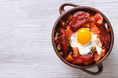 Eggs with chorizo, potatoes and tomatoes in a pot. top view Stock Images