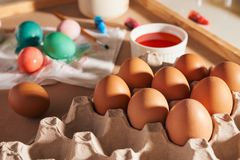 Eggs, colorful paints, brushes, pencils on a wooden background, coloring eggs, preparing for Easter, spring seasonal holiday.  stock photography