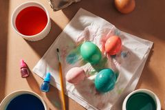 Eggs, colorful paints, brushes, pencils on a wooden background, coloring eggs, preparing for Easter, spring seasonal holiday.  stock images