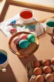 Eggs, colorful paints, brushes, pencils on a wooden background, coloring eggs, preparing for Easter, spring seasonal holiday.  royalty free stock photography