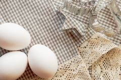 Eggs and cookie cutters on a traditional checkered cloth Stock Photos