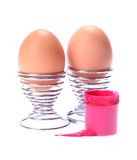 Eggs in cups with pot of paint Royalty Free Stock Photos