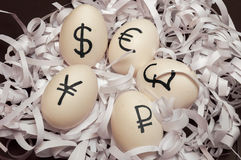 Eggs with currency signs. Of dollar, euro, yen, pound and ruble lying in paper stripes Royalty Free Stock Image
