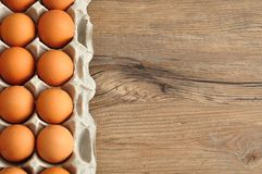 Eggs displayed in a carton. On a wooden table Royalty Free Stock Image