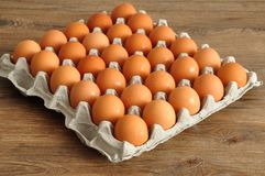 Eggs displayed in a carton. On a wooden table Stock Photo