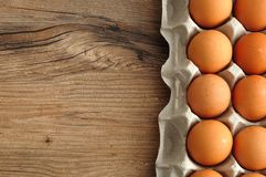 Eggs displayed in a carton. On a wooden table Stock Image
