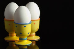 Eggs in dotted eggcups on black. Chicken eggs in dotted eggcups on reflecting black background Royalty Free Stock Photography