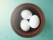 Eggs in an earthenware dish. On a wooden table Stock Photography