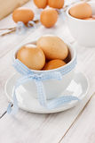 Eggs easter with a blue ribbon in white cup. On a wooden background Royalty Free Stock Image