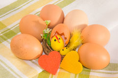 Eggs with easter decoration and felt hearts on cotton napkin. Royalty Free Stock Photography