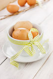Eggs easter with a yellow ribbon in white cup. On a wooden background Royalty Free Stock Image