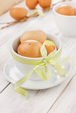 Eggs easter with a yellow ribbon in white cup. On a wooden background Royalty Free Stock Images