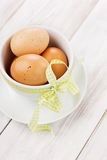 Eggs easter with a yellow ribbon. On a white wooden background Royalty Free Stock Image