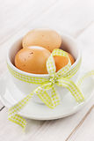 Eggs easter with a yellow ribbon. On a white wooden background Royalty Free Stock Photo
