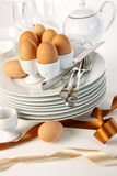 Eggs in egg cups on a pile of plates with ribbons Stock Photos