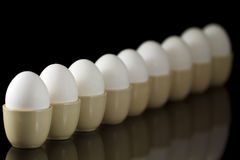 Eggs in egg-cups in a row Royalty Free Stock Photography