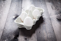 Eggs in a eggbox. On a black wooden table Stock Photos