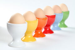 Eggs in eggcups. Close-up of a row of colorful eggcups with brown chicken eggs. Shallow dof Royalty Free Stock Photo
