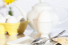 Eggs in Eggcups Breakfast Setting. White eggs in eggcups with additional eggs in bright yellow egg holder and white teapot blurred in background Royalty Free Stock Images