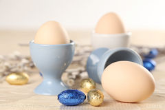 Eggs in eggcups and chocolate easter eggs Stock Image