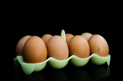 Eggs. Eight eggs in green plastic bucket on black background Royalty Free Stock Images