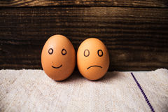 Eggs with emotions on wooden background Stock Photos