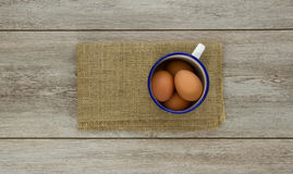 Eggs in enamel cup on burlap Stock Images