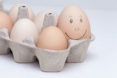 Eggs face drawing on egg. Smiling and satisfied egg, the biggest egg among another little. Concept main, leader, important stock photos