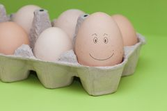 Eggs face drawing on egg. Smiling and satisfied egg, the biggest egg among another little. Concept main, leader, important royalty free stock images