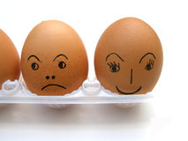 Eggs with faces. Two brown chicken eggs, one with a painted happy face, the other one with an angry face isolated on white studio background Royalty Free Stock Images