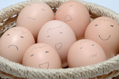 Eggs with Faces in Basket Stock Photos