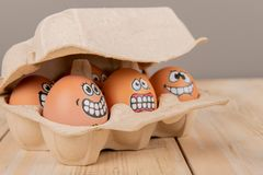 Eggs with faces. In cardboard container royalty free stock images