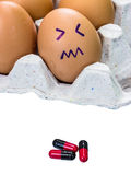 Eggs with faces and medicine Stock Photo