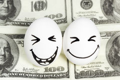 Eggs with faces on money Royalty Free Stock Images