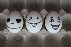 Eggs with faces photo for your design. in the box Royalty Free Stock Photography