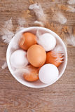Eggs and feathers on wooden table Royalty Free Stock Images