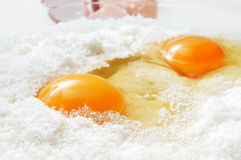 Eggs and flour. Closeup of some cracked eggs on a pile of wheat flour Stock Photography
