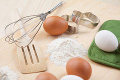 Eggs, flour, cookie mold and whisk on wooden board Royalty Free Stock Photo
