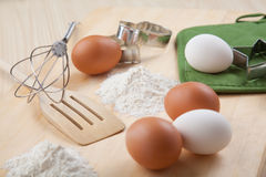 Eggs, flour, cookie mold and whisk on wooden board Stock Images