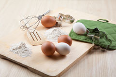 Eggs, flour, cookie mold and whisk on wooden board Royalty Free Stock Photography