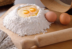 Eggs and  flour on cutting board Royalty Free Stock Photography