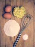 Eggs, flour and other raw materials on a wooden board Royalty Free Stock Photos