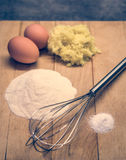 Eggs, flour and other raw materials on a wooden board Royalty Free Stock Image