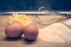 Eggs, flour and other raw materials on a wooden board Stock Photo