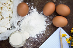 Eggs, flour, sour cream, cottage cheese and notepads recipes. Are on the table Royalty Free Stock Photo