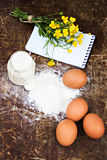 Eggs, flour, sour cream, notepads recipes. Are on the table Royalty Free Stock Photography