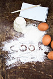 Eggs, flour, sour cream, notepads recipes. On the table Royalty Free Stock Images