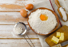 Eggs, flour, sugar, butter on a white  wooden background Royalty Free Stock Photography